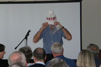 Richard Grundy models a hat during the auction.