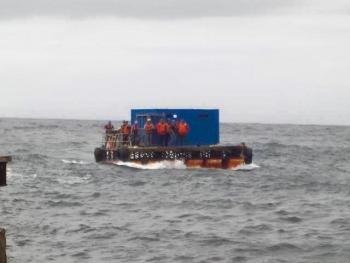 The container with the bulls is ferried ashore on the raft.