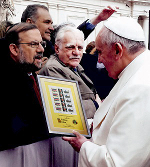 Pope Francis admires a framed sheet of Tristan da Cunha stamps that was presented to him during a public audience in the Vatican City