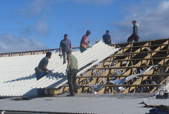 A new roofing sheet being moved into place